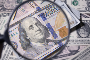 magnifying glass lies on american dollars