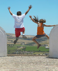 Two children jumping in the countryside. Spain
