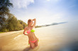 blonde girl in swimsuit stands in shallow sea   against sun