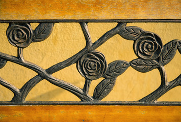 close up curved steel beautiful rose on yellow park bench.