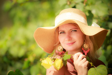 blonde girl in straw hat poses with flowers