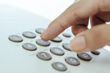 Woman finger touching telephone keypad