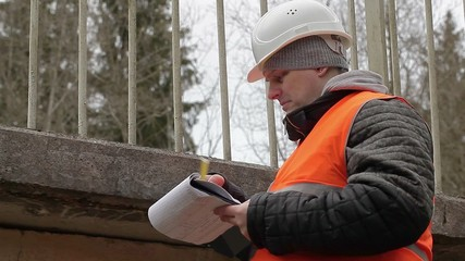 Engineer with tape measure and documentation near the bridge