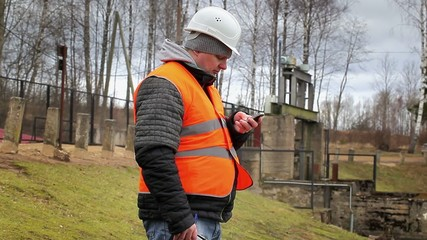 Engineer with cell phone at power plant sluice