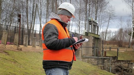Engineer with documentation at power plant sluice