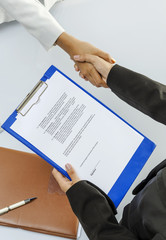 Businesswomen handshaking before signing contract