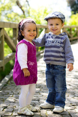 Two little adorable kids in the park, smiling at the camera