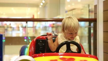 little blonde child happy sitting in toy car