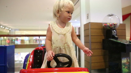 blonde child asks mother to get off toy car