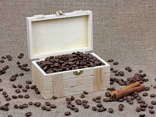 coffee beans and cinnamon in a wooden box on canvas