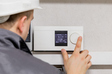 Engineer adjusting thermostat for automated heating system