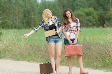 Students girls hitchhike with cardboard on road