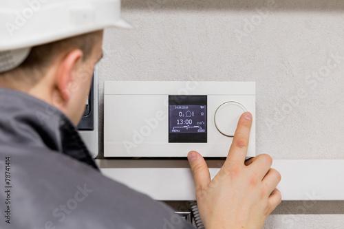 Leinwandbild Motiv Engineer adjusting thermostat for automated heating system
