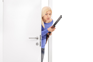Terrified woman holding a rifle and entering a room
