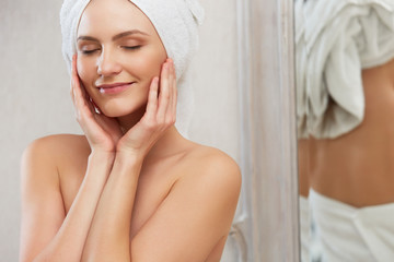 Spa Woman. Portrait of smiling young woman in towel in bathroom.
