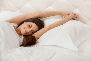 Woman stretching in her bed. A Girl Waking Up in The Morning