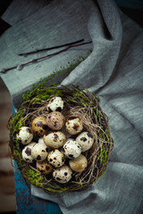 Easter decoration - a nest with quail eggs - on an old wooden ta