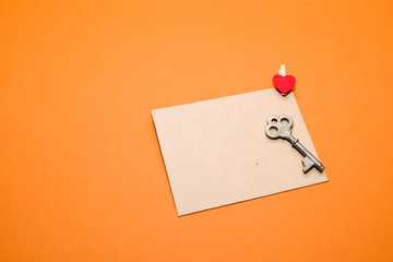 Envelope with heart and key  on a orange  background.