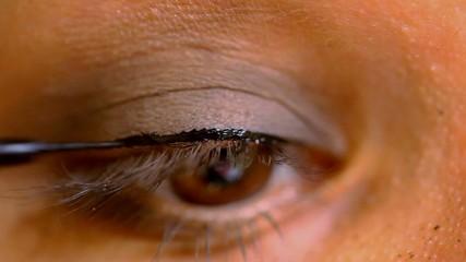 Female brown eye doing make-up. Macro video