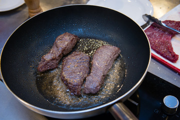 Frying stewed steaks on hot fraying pan