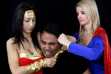 deux femmes habillées en super héro frappant un homme