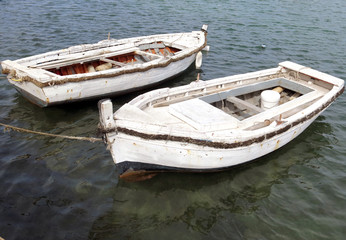 two white old boats in the middle of the water