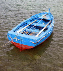 blue and red boat in the middle of the ocean