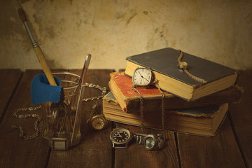 Old clocks, books, glass, tools on a wooden background