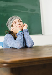 Unglückliches Mädchen sitzt im Klassenzimmer