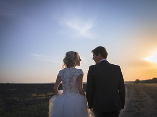 Young wedding couple talking on the field at sunset. Newlyweds b