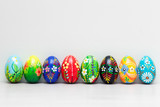 Hand-painted Easter eggs on white rustic wall. Spring patterns
