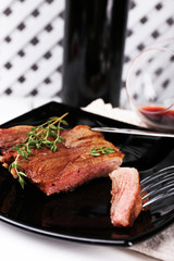 Steak with herbs on plate with wine on wooden background