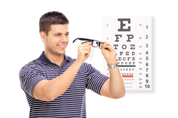Man wiping his glasses in front of an eye chart