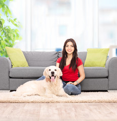 Woman sitting by a sofa with her dog at home