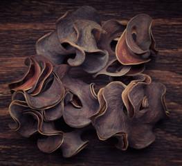 A black unrecognizable dry plant on a wooden vintage background