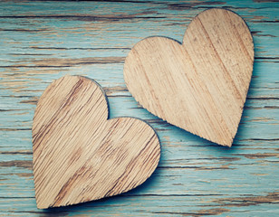 Two wooden hearts placed nicely on a turquoise vintage wood back