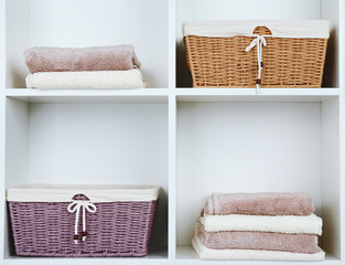 Pile of towels with wicker basket on shelves of rack background