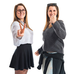Twin sisters doing victory gesture