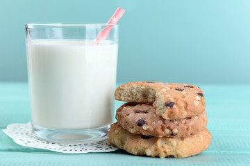 Tasty cookies and glass of milk on color wooden background