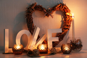 Romantic still life with wicker heart and candle lights