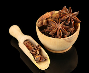Star anise in wooden bowl, isolated on white