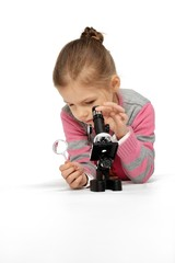Little girl looking through a microscope.