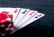 four aces high on black table with chips