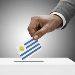Black male holding flag. Voting concept - Uruguay