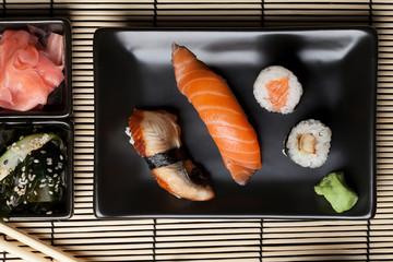 Japanese sushi: nigiri and maki on black plate.