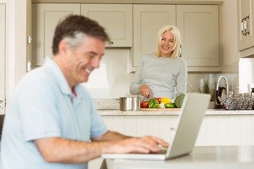 Happy mature man using laptop while wife prepares vegetables