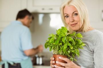 Mature blonde smiling at camera holding basil plant