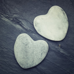 Two white zen hearts shaped rock on a tile background