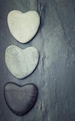 Black,grey,white zen hearts shaped rock on a tile background