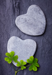 Two grey heart shaped rocks with three lucky clovers on  tile ba